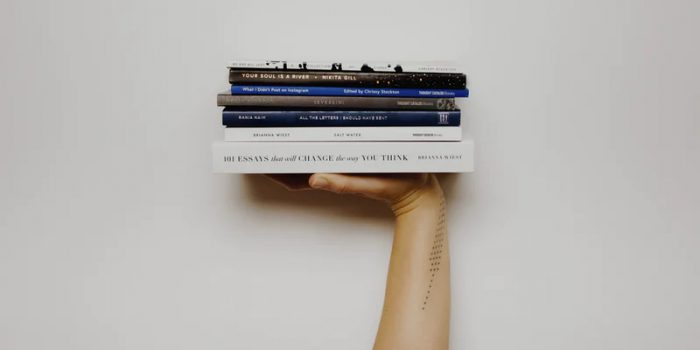 hand holding up a pile of books